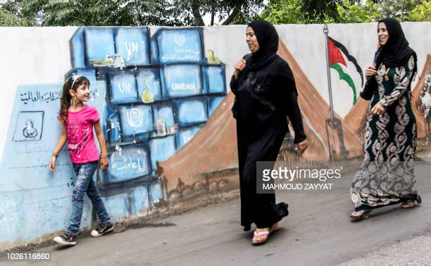 Women and a girl walk past a mural depicting a mock identity card for the Palestinian Ministry for Refugee Affairs next to blocks bearing the logos...