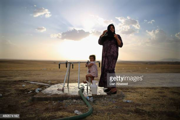 Women and a girl wash at a tap at a temporary displacement camp set up next to a Kurdish checkpoint on June 13, 2014 in Kalak, Iraq. Thousands of...