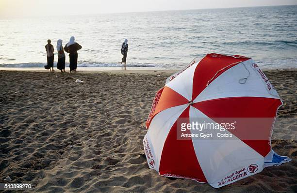 Women and a red and white umbrella on a beach in Algeria