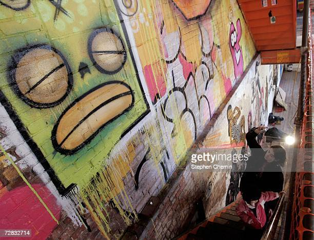A women and child climb the stairs past street art that adorns walls at the Wooster on Spring street art exhibit December 15 2006 at 11 Spring Street...