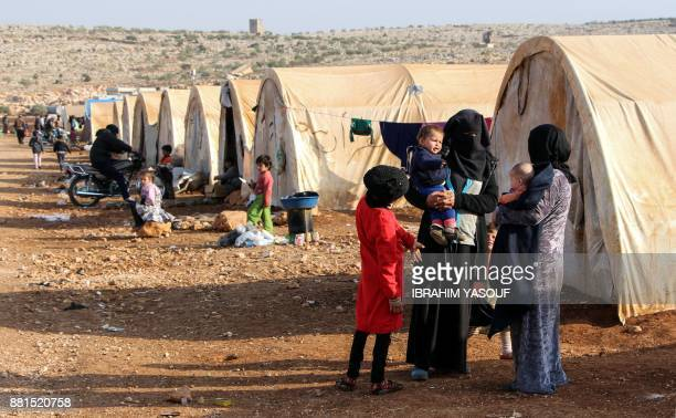 Women and children converse as they stand outside tents at the Furat camp for the displaced from Deir Ezzor north of the town of Kafr Dariyan in the...