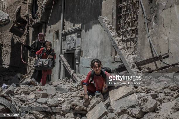 Women and children emerge from the rubble of al-Nuri mosque complex on June 29 in Mosul, Iraq. The Iraqi Army, Special Operations Forces and...