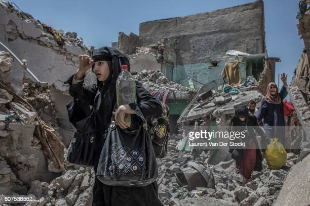 Women and children emerge from the rubble of alNuri mosque complex on June 29 in Mosul Iraq The Iraqi Army Special Operations Forces and...