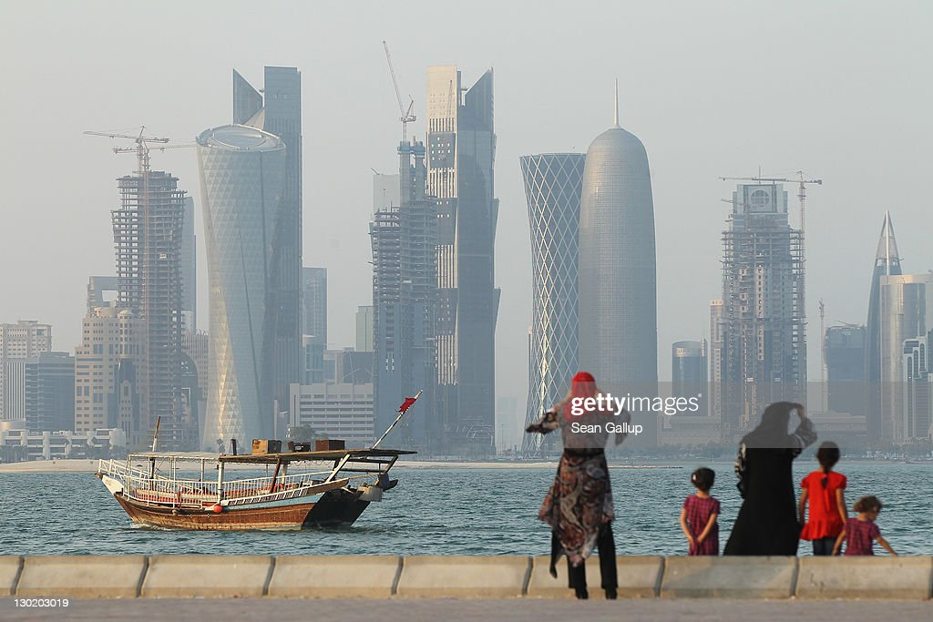 Women and children enjoy the waterfront along the Persian Gulf across from new, budding financial district skyscrapers as a traditional Arab ship passes by on October 24, 2011 in Doha, Qatar. Qatar will host the 2022 FIFA World Cup football competition and is slated to tackle a variety of infrastructure projects, including the construction of new stadiums.