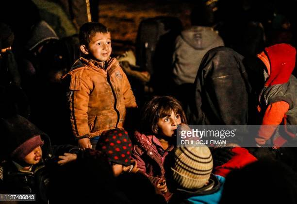 TOPSHOT Women and children evacuated from the Islamic State group's embattled holdout of Baghouz wait in a zone held by the USbacked Syrian...