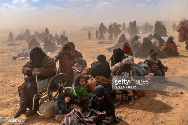 Women and children evacuated from the Islamic State group's embattled holdout of Baghouz sit at a screening area held by the US-backed Kurdish-led...
