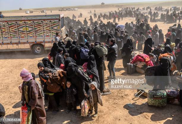Women and children evacuated from the Islamic State group's embattled holdout of Baghouz arrive at a screening area held by the US-backed Kurdish-led...