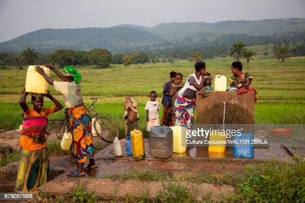 women and children filling containers at community water pump, masango, cibitoke, burundi, africa - east africa stock photos and pictures