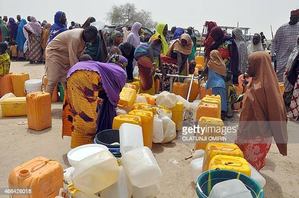 Women and children fleeing from Boko Haram attacks fetch water from a borehole at Gudumariya Refugees Camp Diffa in Niger Republic on March 13 2015...