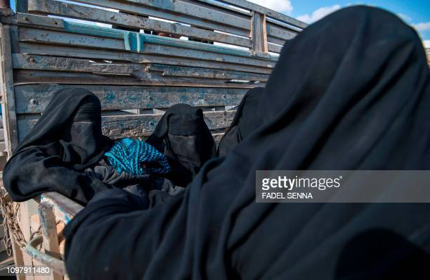 TOPSHOT Women and children fleeing from the last Islamic State group's tiny pocket in Syria sit in the back of a truck near Baghuz eastern Syria on...