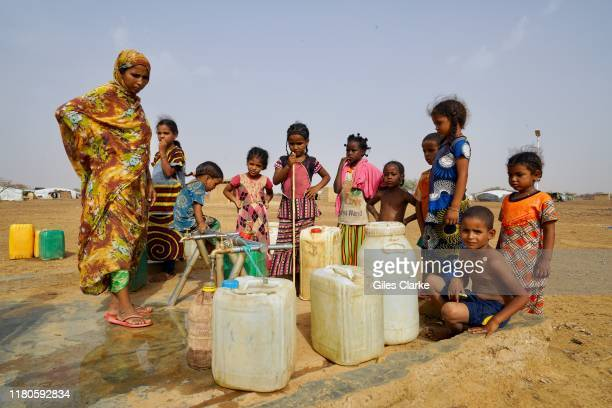 Women and children gather water at an IDP settlement in northern Burkina Faso.