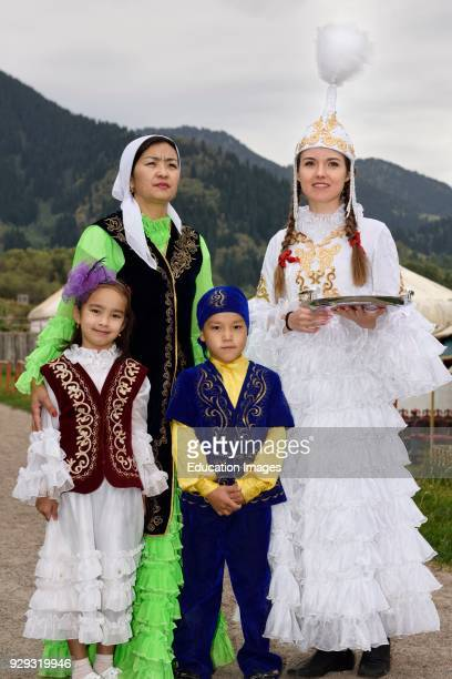 Women and children in traditional Kazakh clothes greeting quests with Shashu candies at Huns village