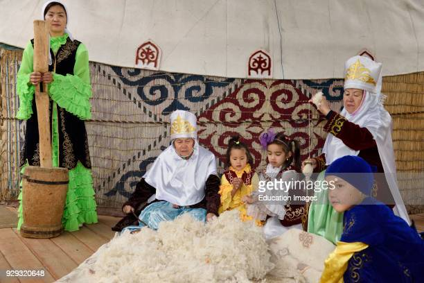 Women and children in traditional Kazakh clothes working wool into felt and yarn Huns Village Kazakhstan
