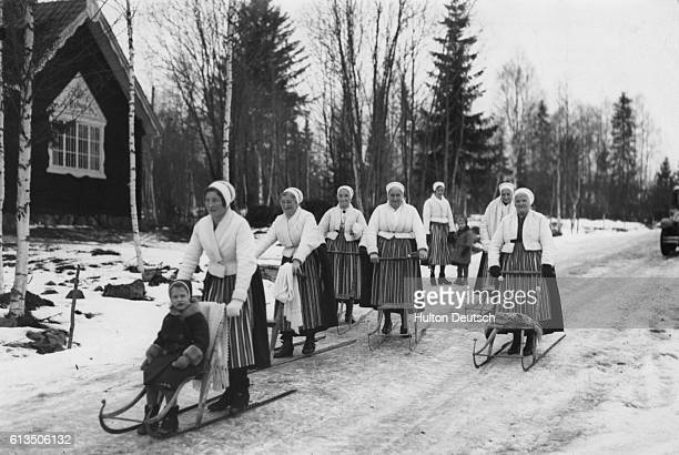 Women and children make their way by sled to their local rectory to attend a formal religious discussion with their vicar. The once compulsary...
