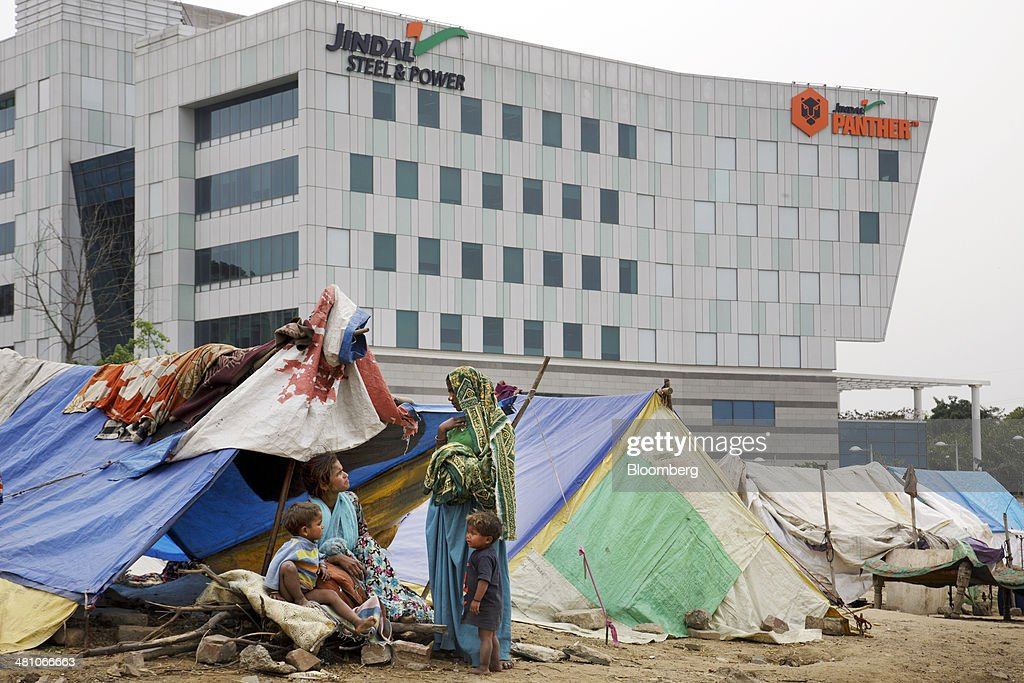 Women and children meet in a laborers' camp in front of a commercial building with Jindal Steel & Power Ltd. and Jindal Panther signage displayed atop the building in Gurgaon, India, on Wednesday, March 26, 2014. Indian stocks rose, sending the benchmark index to a record, after the rupee rose to an eight-month high and sovereign bonds gained on speculation the worlds largest democracy will elect a government capable of reviving economic growth. Photographer: Kuni Takahashi/Bloomberg via Getty Images