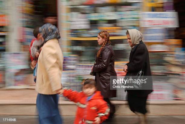 Women and children pass in front of an electronics store January 8 2003 in Diyarbakir the capital of Kurdish areas of Turkey Diyarbakir and the rest...
