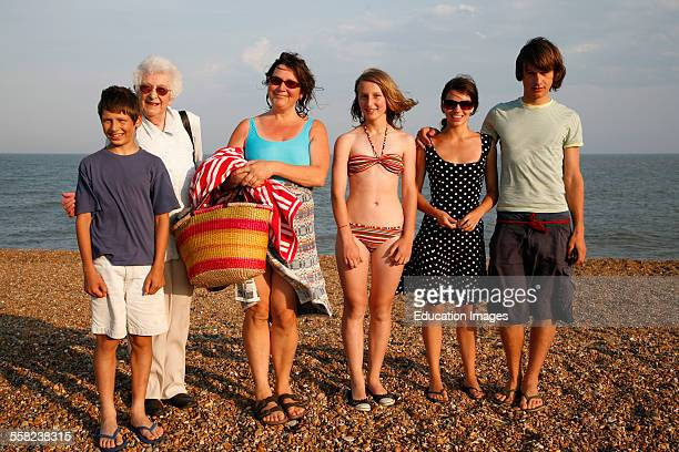 Women and children pose for family snap on a summer beach early evening light Suffolk coast England