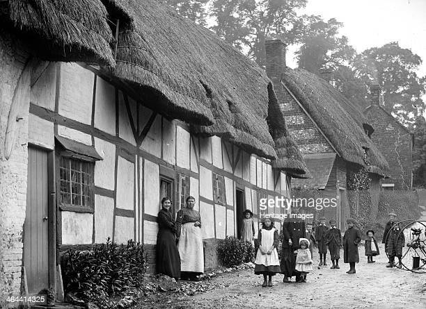 Women and children posing outside a thatched cottage Ramsbury Wiltshire c1860c1922