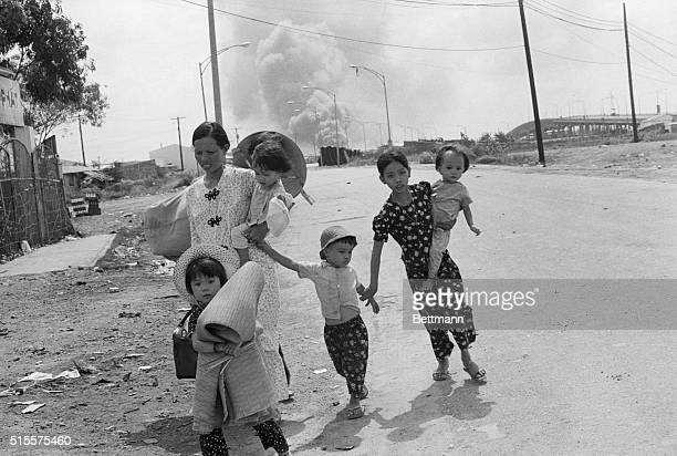 Women and children run from the road as the compound burns in the background on the northern edge of the capital Communist gunners tightened the...