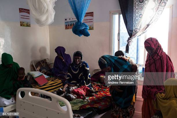 Women and children sit inside the malnutrition ward at Garowe General Hospital on February 27 2017 in Garowe Somalia Somalia is currently on the...
