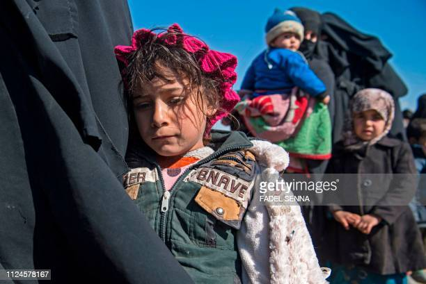Women and children stand in a field after they fled from the Baghouz area in the eastern Syrian province of Deir Ezzor on February 12, 2019 during an...