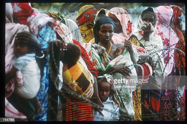 Women and children stand in line at a food distribution site June 20 1993 in Mogadishu Somalia An estimated 350000 Somalis died due to war famine and...