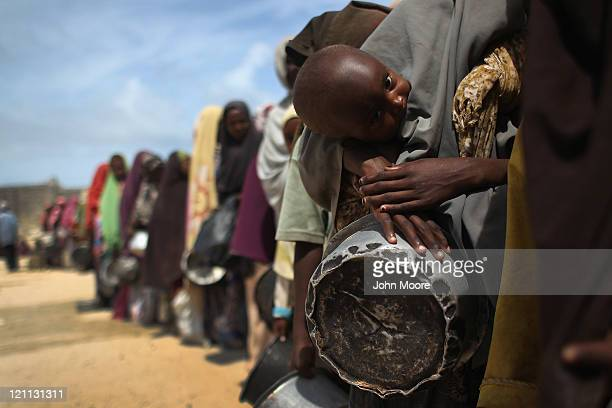 Women and children stand in line for food aid on August 14 2011 in Mogadishu Somalia A local Somali agency distributes cooked porridge from World...