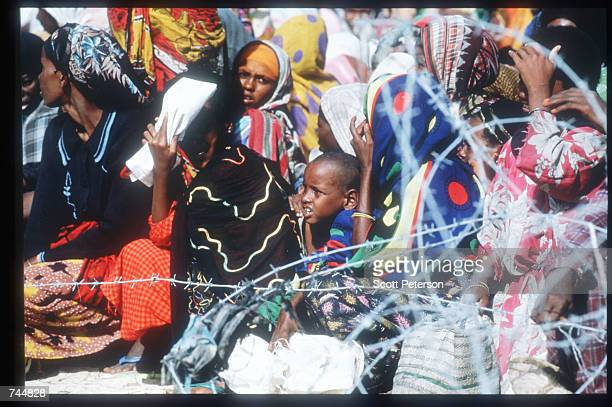 Women and children wait in line at a food distribution site June 20 1993 in Mogadishu Somalia An estimated 350000 Somalis died due to war famine and...