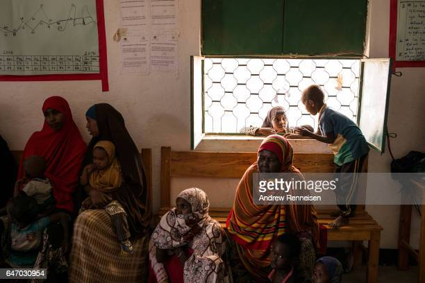 Women and children wait to be checked for signs of malnutrition in a government run health clinic on February 25 2017 in Yaka Somalia Somalia is...