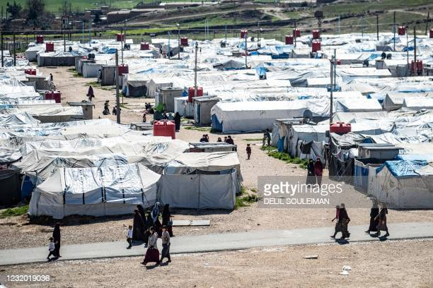 Women and children walk at Camp Roj, where relatives of people suspected of belonging to the Islamic State group are held, in the countryside near...