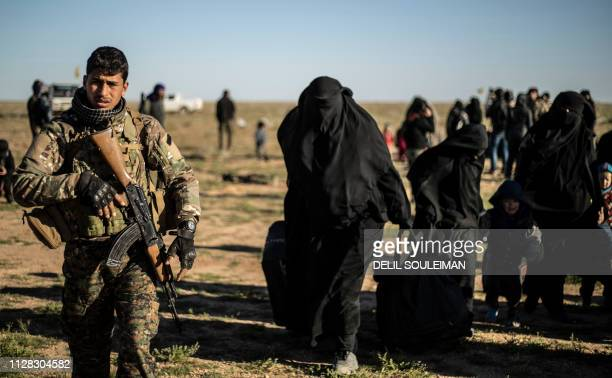 Women and children walk with their suitcases as they are directed by members of the Kurdishled Syrian Democratic Forces after leaving the Islamic...