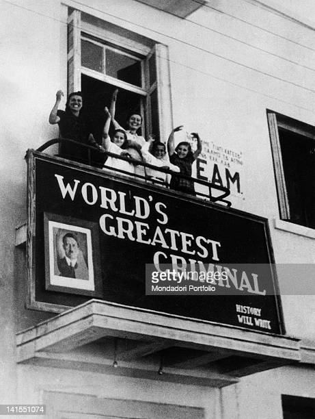 Women and children waving Greek troops passing through from a balcony A sign describes Adolf Hitler as 'World's greatest criminal' Corinth October...