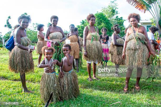 Women and children wear traditional dress as people queue to vote at a polling station in the capital Buka in an historical independence vote on...