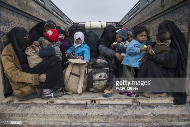 TOPSHOT Women and children who fled the Islamic State group's embattled holdout of Baghouz on February 14 wait in the back of a truck in the eastern...