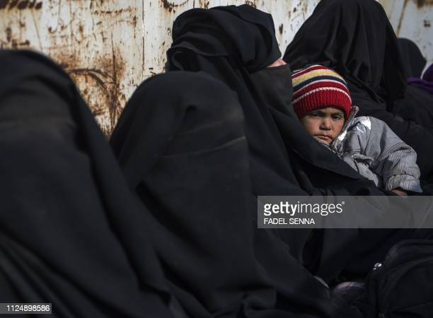 TOPSHOT Women and children who fled the Islamic State group's embattled holdout of Baghouz on February 14 sit waiting in the back of a truck in the...