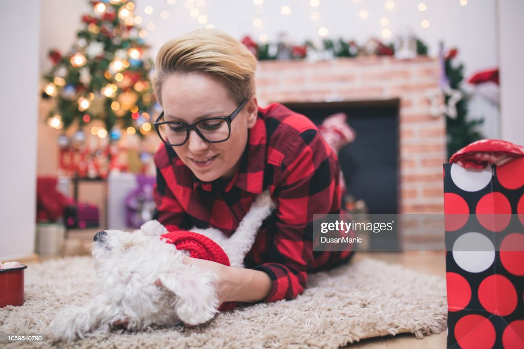 Women and dog enjoying in cuddling in Christmas time : Stock Photo