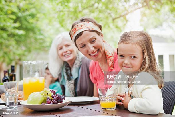 Women and girl (6-7 years) at garden table