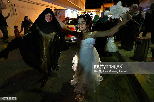 Women and girls dance in front a bridal car as it makes its way to the Baghdad Hotel in the AlSadoon area of Baghdad Iraq October 16 2014 Twentythree...