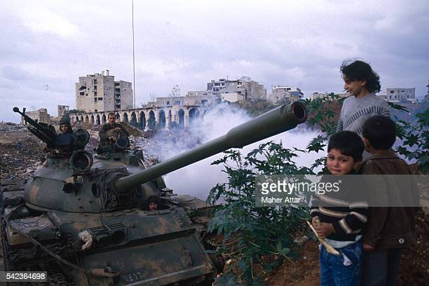 Women and her children stand near a T54 Syrian tank in Ras Elnabeh.