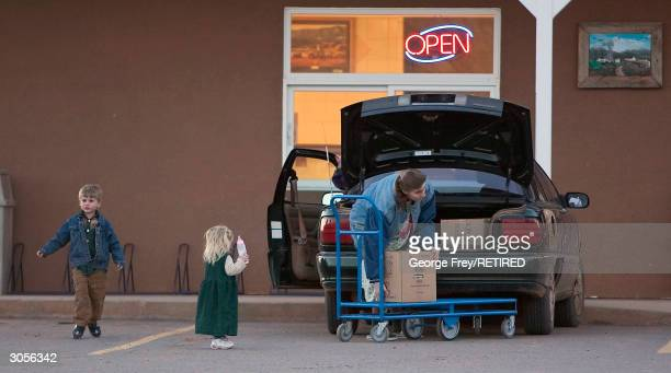 A women and her small children load boxes into her car in Colorado City Arizona the home of the Fundamentalist Church of Jesus Christ of Latter Day...
