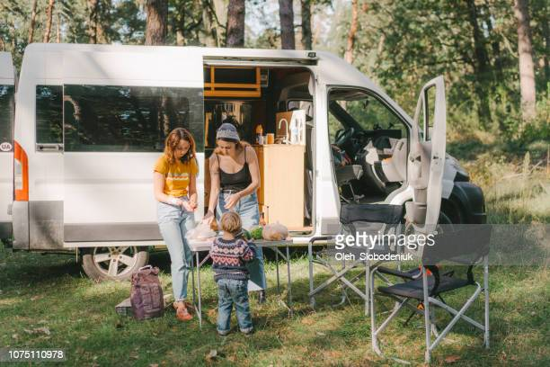 women and little boy  cooking burger on grill in forest - camping stock pictures, royalty-free photos & images