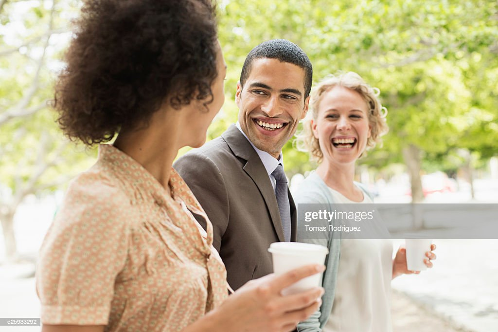 Women and man having coffee break in park : Stockfoto