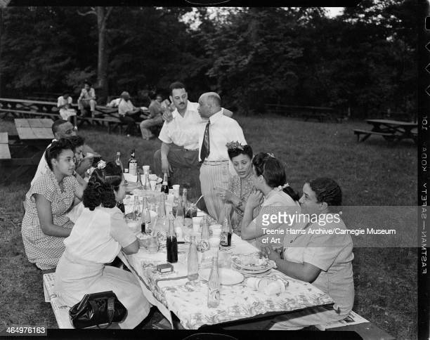 Women and men including woman second from left wearing eyeglasses and gingham dress and man wearing ribbon on belt gathered around picnic table in...