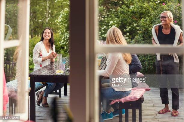Women and teenage girl at dining table seen from window