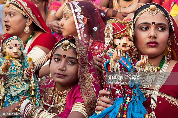 CONTENT] Women and young girls wearing their most beautiful saris and jewelry holding small idols of Shiva and Gauri during Gangaur and Mewar...