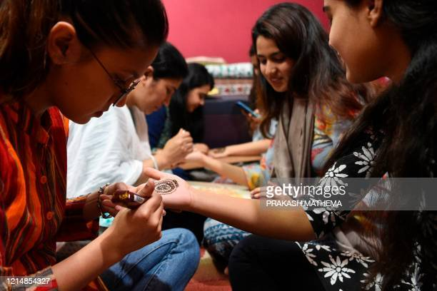 Women applies henna on their hands during 'Chand Raat' or 'Night of the Moon' in Kathmandu on May 24 on the eve of Eid alFitr festival Muslims around...