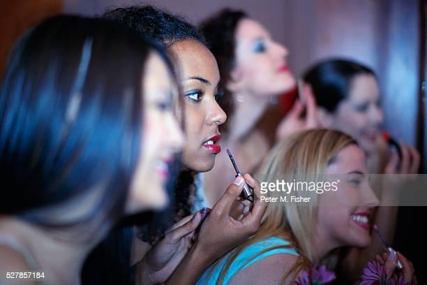 Women Applying Makeup in Powder Room