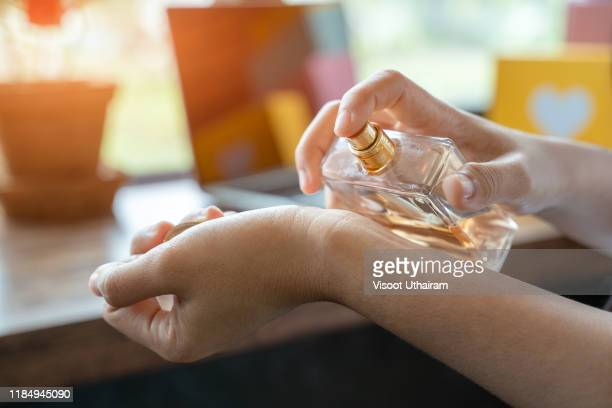 women applying perfume on her wrist. - perfume stock pictures, royalty-free photos & images