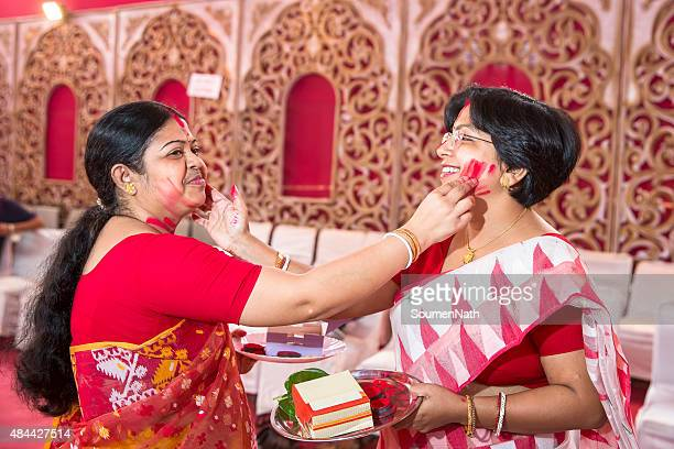 Mujer aplicar ritualistic Vermilion en sí durante Durga Puja