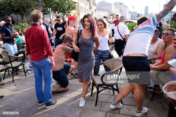 Women are applauded as they walk past England fans in the port area of Marseille on June 9 ahead of the start of the Euro 2016 football tournament in...